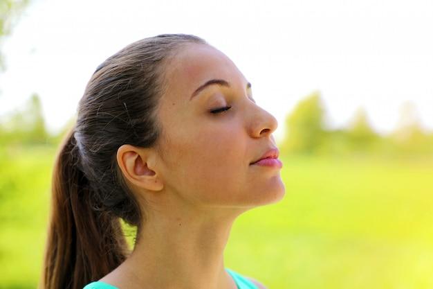 Schließen sie herauf porträt der frau, die entspannend frische luft tief im park atmet.