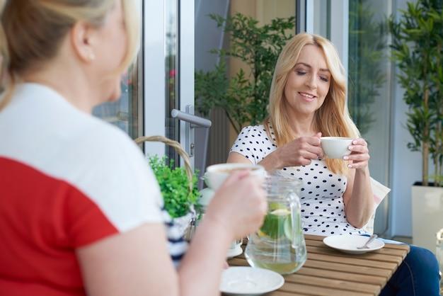 Schließen sie herauf porträt der frau, die kaffee auf dem balkon trinkt