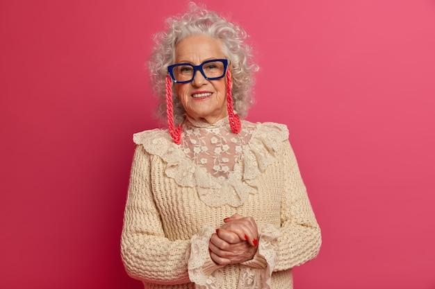 Schließen sie herauf porträt der glücklichen faltigen modischen oma, die brille und pullover trägt