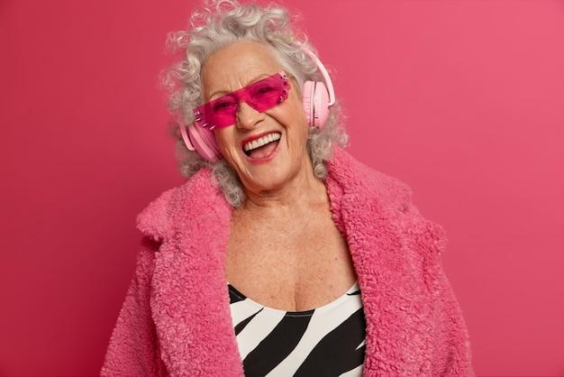 Schließen sie herauf porträt der glücklichen faltigen modischen oma, die rosa strumpfhosen und mantel trägt