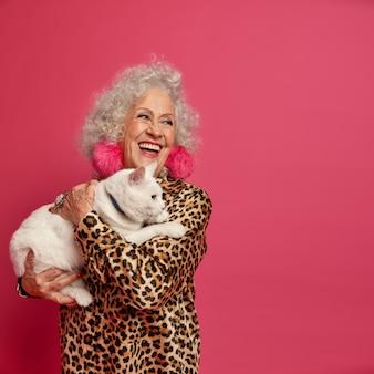 Schließen sie herauf porträt der glücklichen faltigen modischen oma mit der schönen katze