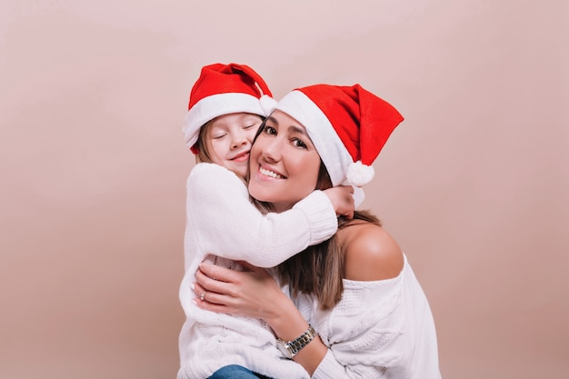 Schließen sie herauf porträt der glücklichen familie, die weihnachtsmützen und weiße pullover trägt, sie umarmen und zeigen wirklich glückliche gefühle. isolierte wand, platz für text
