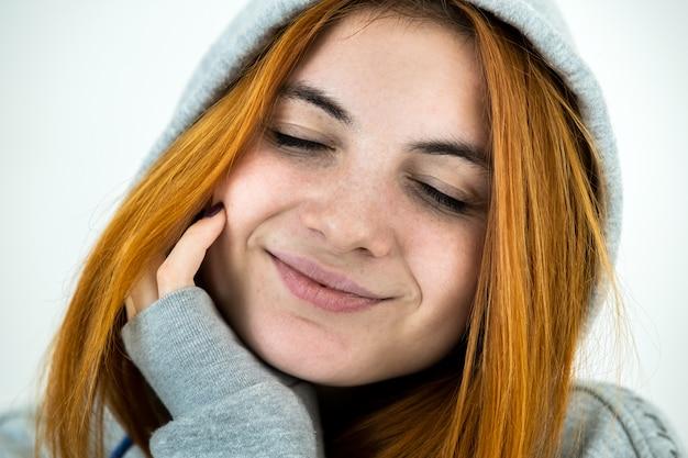 Schließen sie herauf porträt der glücklichen lächelnden jungen rothaarigen frau, die warmen hoodie-pullover trägt