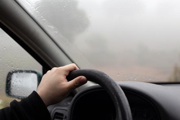 Schließen sie herauf porträt der hand eines nicht erkennbaren mannes, der das lenkrad eines autos während einer reise an einem nebligen und regnerischen wintertag fährt