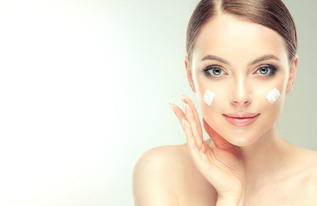 Schließen sie herauf porträt der herrlichen, jungen, braunhaarigen frau mit flecken der kosmetischen creme