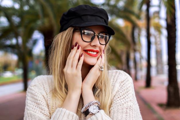 Schließen sie herauf porträt der hübschen blonden frau, die trendiges lässiges outfit, roten lippenstift und klare brille, maniküre und schmuck trägt, überraschte emotionen, posiert auf der straße mit palmen, reisen allein.
