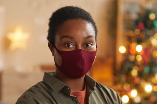 Schließen sie herauf porträt der jungen afroamerikanischen frau, die maske trägt und kamera betrachtet, während weihnachten zu hause feiern, raum kopieren