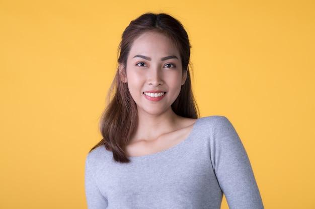Schließen sie herauf porträt der jungen asiatischen glücklichen frau lokalisiert auf gelber wand