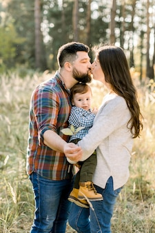 Schließen sie herauf porträt der jungen attraktiven familie mit dem kleinen kleinen sohn, der im schönen herbstkiefernwald am sonnigen tag aufwirft