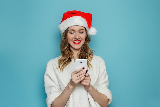 Schließen sie herauf porträt der jungen frau in der weihnachtsmütze und im weißen winterpullover, die lächeln und in das handy schauen