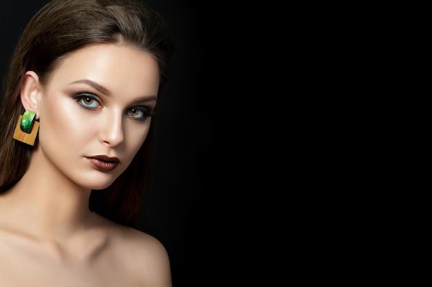 Schließen sie herauf porträt der jungen frau mit braunen lippen und grünen rauchigen augen über schwarzem hintergrund.