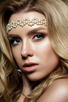 Schließen sie herauf porträt der jungen frau mit den rauchigen augen der bronze, die weißes perlenhaarband tragen. modernes braut make-up.