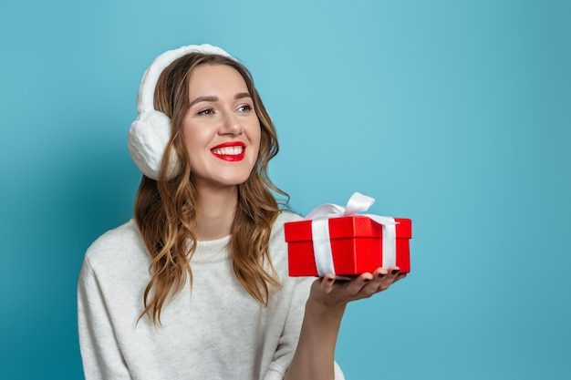 Schließen sie herauf porträt der jungen glücklichen lächelnden kaukasischen frau im weißen winterpullover, der rote geschenkbox in ihren händen lokalisiert auf blauer wand hält