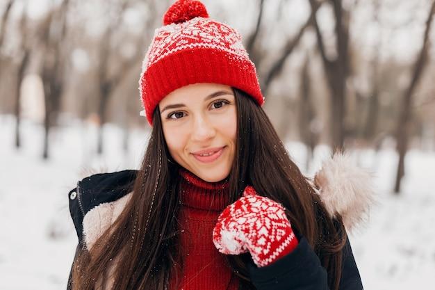 Schließen sie herauf porträt der jungen hübschen offenen lächelnden glücklichen frau in den roten handschuhen und in der gestrickten mütze, die mantel trägt, der im park im schnee spielt, warme kleidung, spaß hat