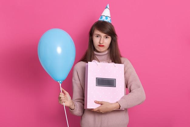 Schließen sie herauf porträt der jungen schönen dunkelhaarigen frau mit geschenk und blauem ballon