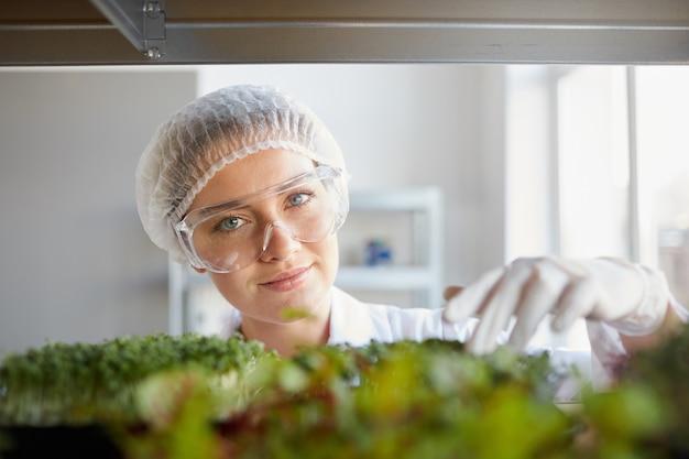 Schließen sie herauf porträt der jungen wissenschaftlerin, die kamera betrachtet und pflanzenproben während der arbeit im biotechnologielabor, kopierraum untersucht
