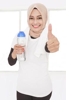 Schließen sie herauf porträt der muslimischen sportlichen frau, die eine flasche mineralwasser hält und daumen aufgibt