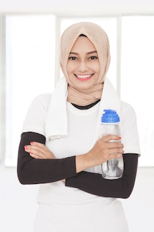 Schließen sie herauf porträt der muslimischen sportlichen frau, die eine flasche mineralwasser hält