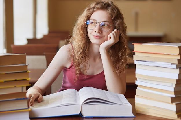 Schließen sie herauf porträt der nachdenklichen attraktiven studentin mit foxy lockigem haar, in den gläsern, die zwischen verschiedenen büchern am tisch sitzen
