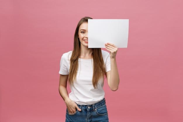 Schließen sie herauf porträt der positiven lachenden frau, die weißes und großes weißes modellplakat lächelt und hält