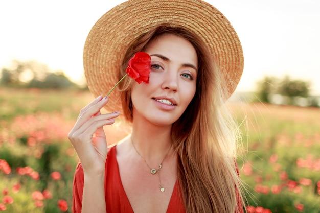 Schließen sie herauf porträt der reizenden jungen romantischen frau mit mohnblume in der hand, die auf feldhintergrund aufwirft. strohhut tragen. weiche farben.