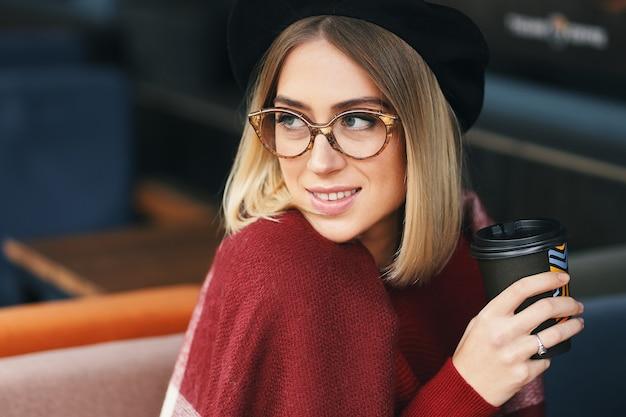 Schließen sie herauf porträt der reizenden romantischen lächelnden frau, die kaffee von hand hält und brille, baskenmütze und wollschal trägt
