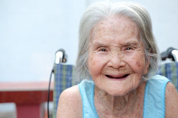 Schließen sie herauf porträt der schönen älteren frau, die auf einem rollstuhl lächelt und sitzt