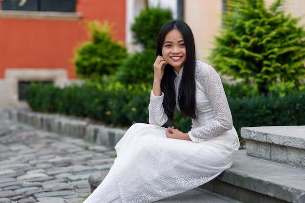 Schließen sie herauf porträt der schönen asiatischen frau gekleidet im weißen kleid von ao dai, das auf der treppe im hof sitzt.