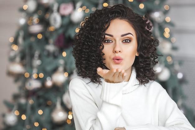 Schließen sie herauf porträt der schönen frau an weihnachten, die einen luftkuss senden