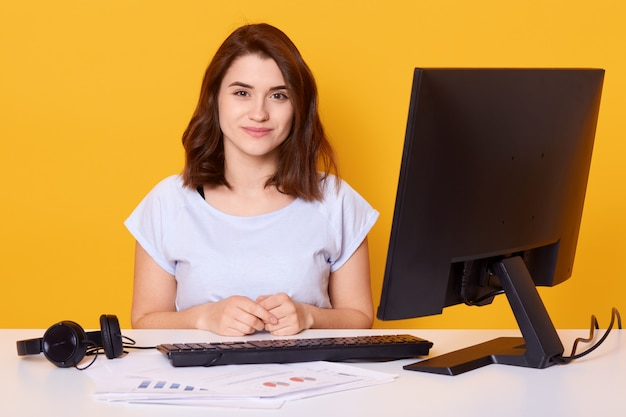 Schließen sie herauf porträt der schönen jungen brünettenfrau, die am weißen schreibtisch vor dem computer zu hause sitzt