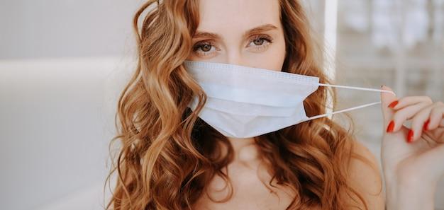 Schließen sie herauf porträt der schönen jungen europäischen frau, die schutzmaske für koronavirus-prävention, hygiene trägt, um die ausbreitung des coronavirus zu stoppen. vermeiden sie es, das covona-19-konzept des corona-virus zu kontaminieren