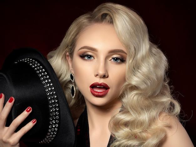 Schließen sie herauf porträt der schönen jungen frau mit mode-make-up. schönes abend make-up - goldene rauchige augen und rote lippen mit glitzer.