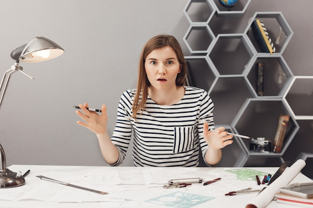 Schließen sie herauf porträt der schönen lustigen jungen europäischen freiberuflichen designerin, die hand in aufgeregtem und schockiertem blick ausbreitet, nachdem sie erkannt hat, dass sie idee über kleidung für nächste modenschau hat
