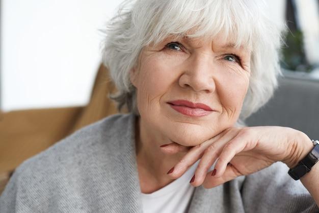 Schließen sie herauf porträt der schönen positiven kaukasischen dame mittleren alters am ruhestand, der zu hause träumt und an ihre enkelkinder denkt. elegante grauhaarige großmutter, die zeit drinnen verbringt