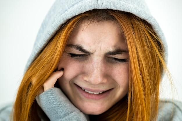 Schließen sie herauf porträt der traurigen depressiven jungen rothaarigen frau, die warmen kapuzenpullover trägt.