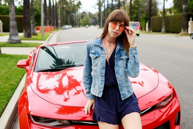 Schließen sie herauf porträt der überraschten brünetten frau, die auf der motorhaube des erstaunlichen roten cabrio-sportwagens in kalifornien sitzt.