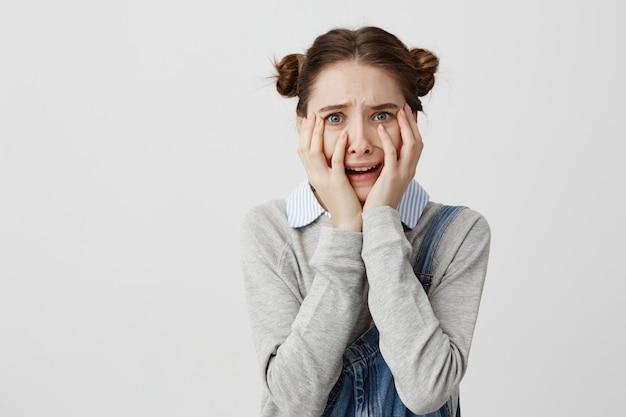 Schließen sie herauf porträt der verängstigten frau im denim, das ihr gesicht mit den händen bedeckt, die geschockt werden. junge frauen, die in panik schreien und in schwierigkeiten sind, können nicht an die wahrheit glauben. emotionskonzept