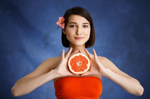 Schließen sie herauf porträt der zarten jungen frau, die geschnittenes orange über blaue wand hält