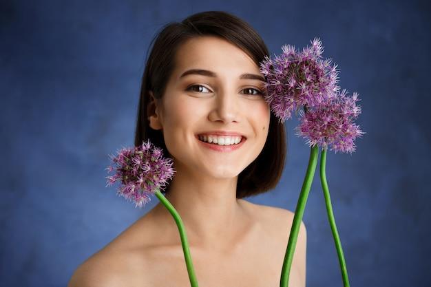 Schließen sie herauf porträt der zarten jungen frau mit lila blumen über blauer wand