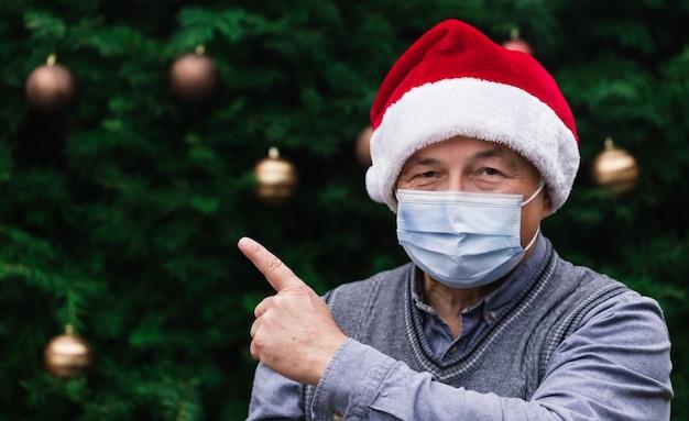 Schließen sie herauf porträt des älteren mannes, der einen weihnachtsmannhut und eine medizinische maske mit emotion trägt und den finger zeigt. vor dem hintergrund eines weihnachtsbaumes. coronavirus pandemie