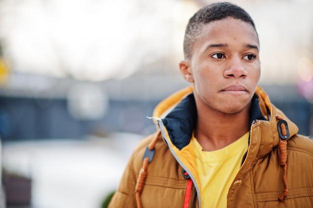 Schließen sie herauf porträt des afrikanischen mannes tragen auf orange jacke bei kaltem wetter im freien gestellt.