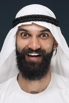 Schließen sie herauf porträt des arabischen saudischen geschäftsmannes auf dunkelblauem studiohintergrund. junges männliches modell stehend und lächelnd, sieht glücklich aus. konzept von geschäft, finanzen, gesichtsausdruck, menschlichen emotionen.
