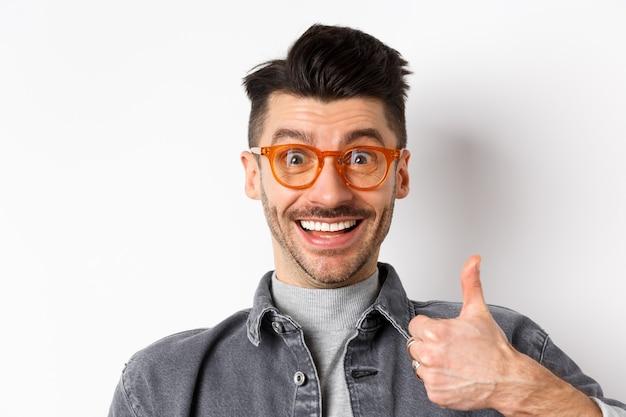 Schließen sie herauf porträt des aufgeregten lustigen kerls in der brille, die daumen oben zeigt, lächelnd unterstützend, lobend und cooles geschäft empfehlen, das auf weißem hintergrund steht.