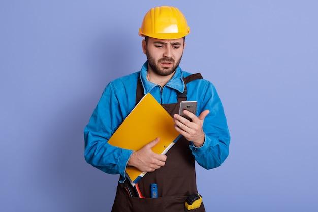 Schließen sie herauf porträt des empörten verwirrten jungen ingenieurs, der smartphone und papierkasten hält, schockierten gesichtsausdruck, nachricht mit schlechten nachrichten erhalten. arbeitsplatzverlust während quaratine. krisenkonzept.