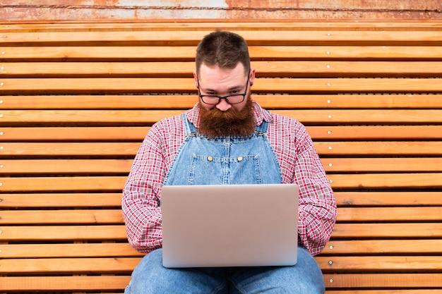 Schließen sie herauf porträt des ernsten brutalen bärtigen hipster-mannes im blauen overall