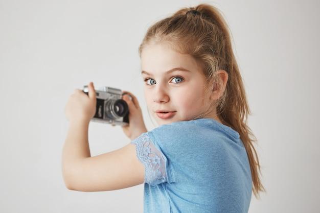 Schließen sie herauf porträt des fröhlichen niedlichen mädchens mit blonden haaren und blauen augen, mit interessiertem ausdruck, der ein selfie nehmen wird.