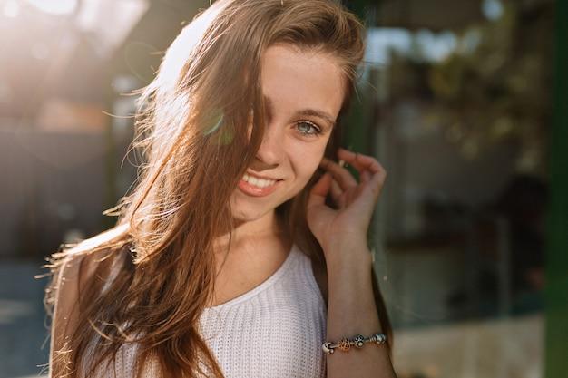 Schließen sie herauf porträt des glücklichen lächelnden mädchens mit langen haaren und blauen augen, die zur kamera im sonnenlicht aufwerfen