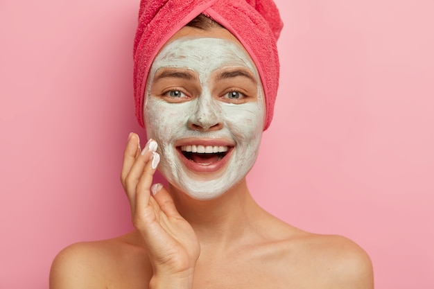 Schließen sie herauf porträt des glücklichen überglücklichen weiblichen modells mit kosmetischer gesichtsmaske, die über ihrem gesicht angewendet wird, hat schönheitsbehandlungen, trägt gewickeltes handtuch auf kopf, hat gesundes erfrischtes aussehen. erneuerung und therapie