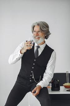 Schließen sie herauf porträt des grinsenden altmodischen mannes. großvater mit einem glas wasser.