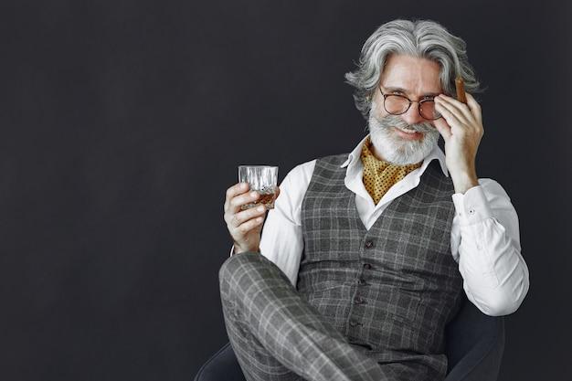 Schließen sie herauf porträt des grinsenden altmodischen mannes. großvater mit zigarre und whisky.